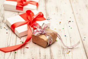 boxex-подарка-с-тонкой-красной-лентой-и-confetti-на-старой-белой-древесине-t-130102440